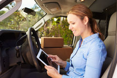 Female Delivery Driver Sitting In Van Using Digital Tablet Royalty Free Stock Photography