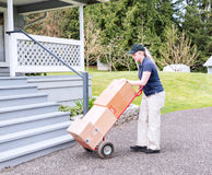 Female delivery person with handtruck and boxes making a deliver Stock Photo
