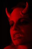 Female Demon. Photo of a female demon with horns and fangs stock photo