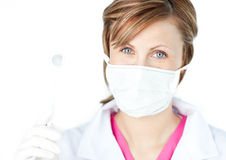Female dental surgeon wearing a mask. Against white background royalty free stock image