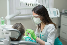 Female Dentist checking little girl patient Stock Photo