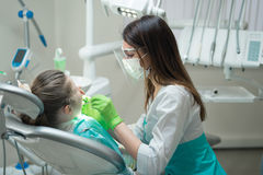 Female Dentist checking little girl patient Stock Photography