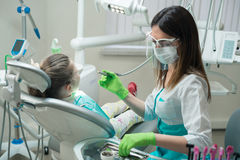 Female Dentist checking little girl patient Royalty Free Stock Photos