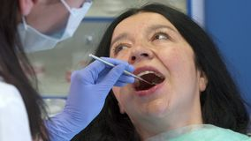 Dentist checks up woman`s teeth. Female dentist checking up woman`s teeth after deep cleaning. Close up of dental hygienist putting mirror into patient`s mouth Royalty Free Stock Image