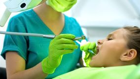 Female dentist drilling teenage girl tooth, caries removal, healthy oral cavity stock image