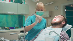 Female dentist drilling tooth of male patient and looking to camera. Slider shot stock video