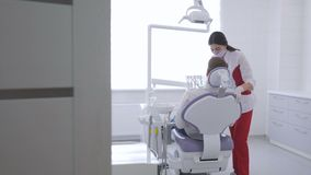 A female dentist examines the oral cavity of a young man sitting in a chair. A female dentist examines the oral cavity of a young man with glasses sitting in a stock video