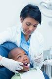 Female dentist examining boys teeth Stock Photos