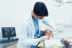 Female dentist examining boys teeth Stock Photography