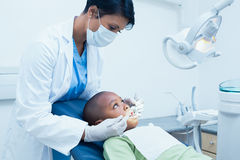 Female dentist examining boys teeth Royalty Free Stock Images
