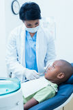 Female dentist examining boys teeth Stock Photography