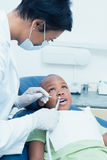 Female dentist examining boys teeth in dentists chair Royalty Free Stock Photography