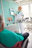 Female dentist examining dental X-ray Stock Image