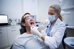 Female dentist examining male patient with teeth shades Royalty Free Stock Photo