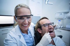 Female dentist examining male patient with tools Stock Image