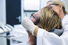 Female dentist examining male patient with tools Royalty Free Stock Image