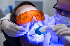 Female dentist examining male patient with tools Stock Photography