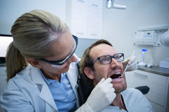 Female dentist examining male patient with tools Royalty Free Stock Photos
