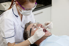 A female dentist examining a male patients teeth, close up Stock Photography