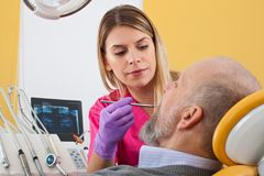 Female dentist examining patient. Young female dentist examining mature male patient with periodontal probe Stock Photo