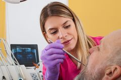 Female dentist examining patient. Young female dentist examining mature male patient with periodontal probe Royalty Free Stock Photos