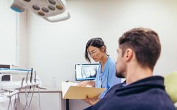 Dentist examining the reports of patient in clinic. Female dentist examining the reports of male patient in clinic. Dentist in dental office with patient Stock Photos