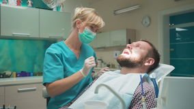 Female dentist examining teeth of male patient, looks to the camera. Slider shot stock video footage