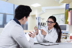 Female dentist explaining drugs at patient Stock Photos