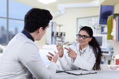 Female dentist explaining pill to patient Stock Photography