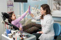 Female dentist and girl patient satisfied after treating teeth at dental clinic office, smiling and doing high-five. Happy female dentist and girl patient Stock Image