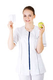 Female dentist with green apple and big tooth Royalty Free Stock Photo