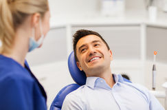 Female dentist with happy male patient at clinic. People, medicine, stomatology and health care concept - female dentist talking to happy male patient at dental Stock Images
