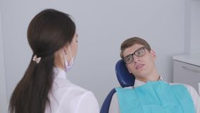 A female dentist is having a conversation with a patient sitting in a dental chair. A female dentist is having a conversation with a patient, a young man with stock video footage