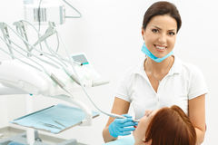 Female dentist and her patient. Female attracrtive dentist and her patient in dental office Royalty Free Stock Images