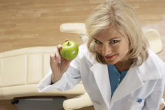 Female dentist holding green apple in dental surgery, smiling, portrait, overhead view Royalty Free Stock Photo