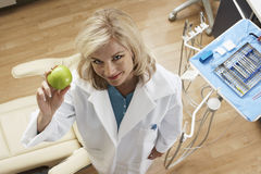 Female dentist holding green apple in dental surgery, smiling, portrait, overhead view Stock Image