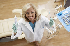 Female dentist holding toothpaste and toothbrush in dental surgery, smiling, portrait, overhead view Royalty Free Stock Photography