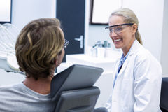 Female dentist interacting with male patient Royalty Free Stock Photo