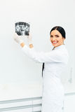 Female Dentist Looking at Dental Xray in Clinic.  stock photo