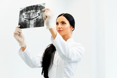 Female Dentist Looking at Dental Xray in Clinic Stock Images