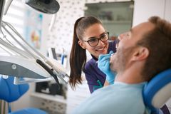 Dentist looking patient`s teeth on dental clinic Stock Photos