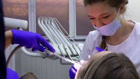 Female dentist is making professional dental cleaning to the patient