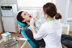 Female dentist with male patient at dental office. Concept of healthy Royalty Free Stock Photos