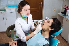 Female dentist with male patient at dental office. Concept of healthy Stock Photos