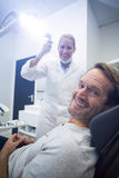 Female dentist and male patient smiling Royalty Free Stock Photography
