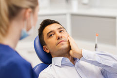 Female dentist and male patient with toothache Stock Photo