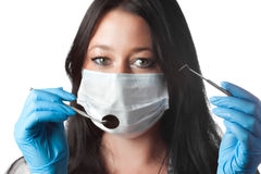 Female dentist in mask holding tool and mirror Stock Images