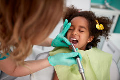 Female dentist patiently polish teeth to child Stock Photos