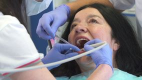 Dentist provides oral irrigation for client. Female dentist providing oral irrigation for senior client. Close up of dental hygienist checking patients teeth by Royalty Free Stock Photo