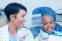 Female dentist showing boy his mouth x-ray Royalty Free Stock Images